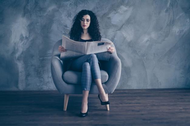 Mulher de negócios com cabelo ondulado sentado na cadeira lendo jornal sobre a parede de concreto Foto Premium