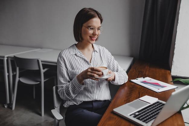 Mulher de negócios com camisa listrada, apreciando seu café da manhã enquanto olha para a tela do computador. Foto gratuita