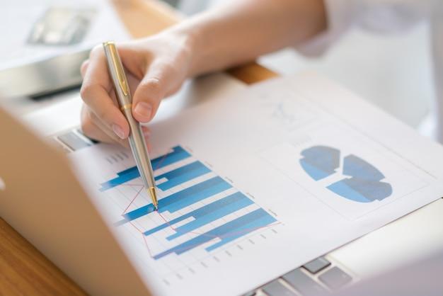 Mulher de negócios com gráficos financeiros e laptop na mesa. Foto gratuita
