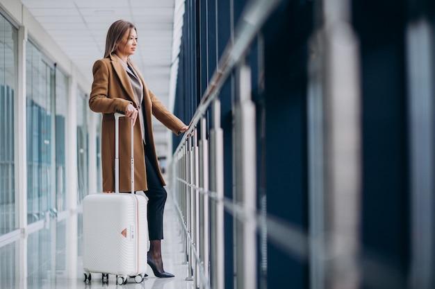 Mulher de negócios com mala de viagem no aeroporto Foto gratuita