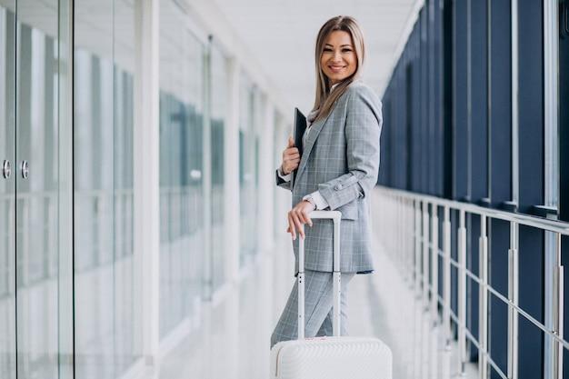Mulher de negócios com malas de viagem no aeroporto, segurando laptop Foto gratuita