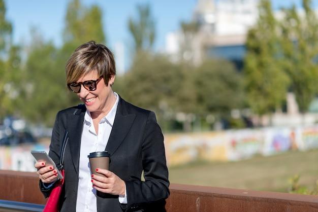 Mulher de negócios com o smartphone que está em uma ponte. Foto Premium