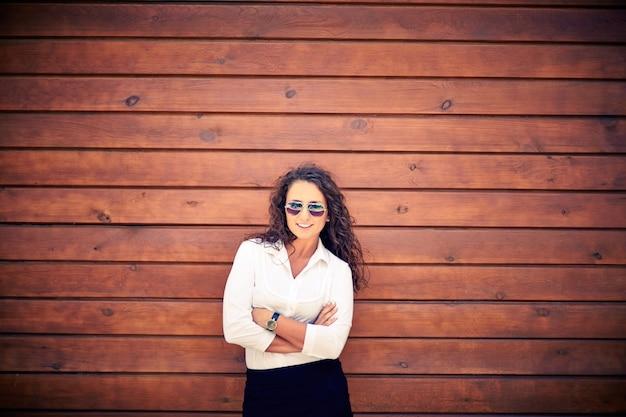 7fd10d58d0cdb Mulher de negócios com óculos de sol com fundo de madeira   Baixar ...