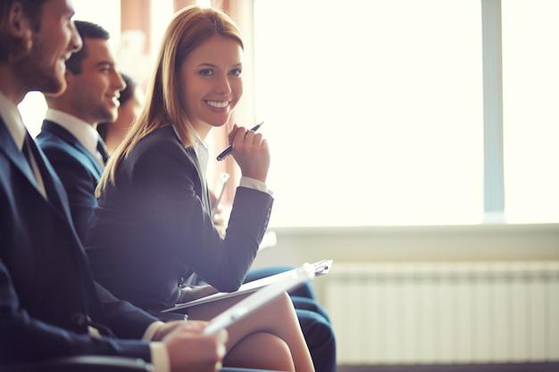 Mulher de negócios com pena de sorriso em uma conferência Foto gratuita