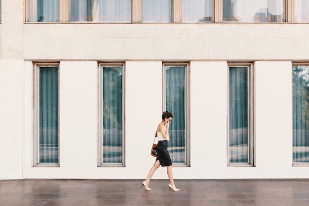 Mulher de negócios com saia de couro, falando ao telefone Foto gratuita