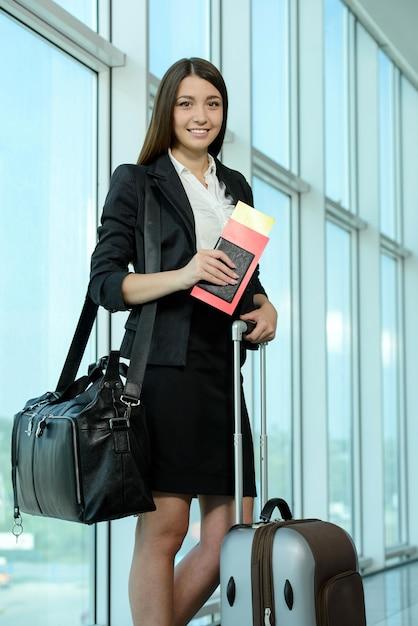 Mulher de negócios em bilhetes de avião à espera de seu vôo. Foto Premium