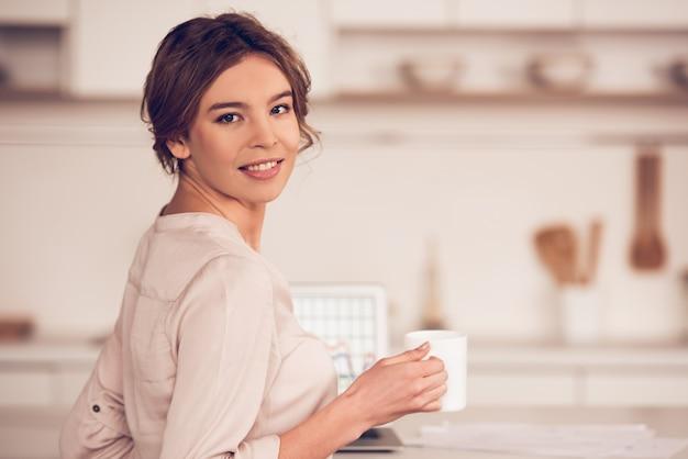 Mulher de negócios em roupas casuais está segurando uma xícara Foto Premium