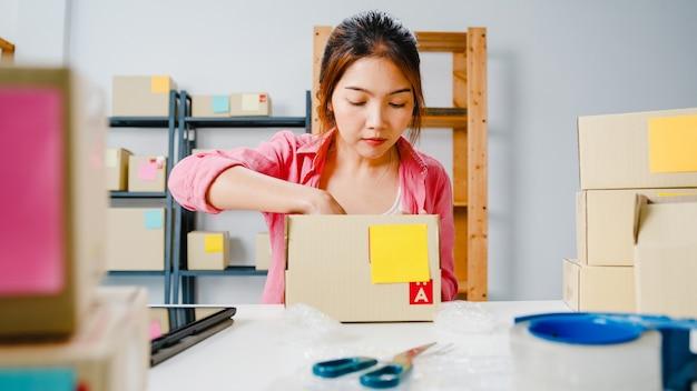 Mulher de negócios empreendedora da ásia jovem embalagem produto em caixa de papelão entregar ao cliente, trabalhando no escritório doméstico proprietário de uma pequena empresa, inicie a entrega no mercado online, conceito freelance de estilo de vida. Foto gratuita