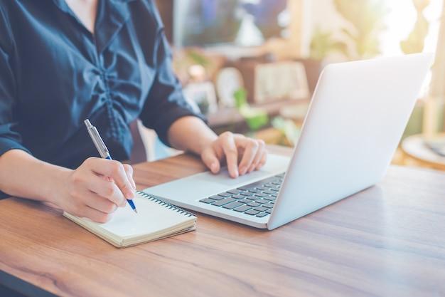 Mulher de negócios está escrevendo em um caderno com uma caneta e usando um laptop para trabalhar no escritório. Foto Premium