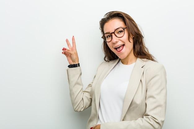 Mulher de negócios europeia jovem alegre e despreocupada mostrando um símbolo de paz com os dedos. Foto Premium