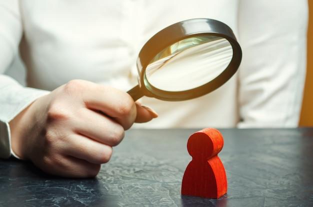 Mulher de negócios examina a figura de um homem vermelho Foto Premium