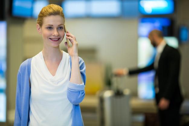 Mulher de negócios falando no celular na sala de espera Foto gratuita