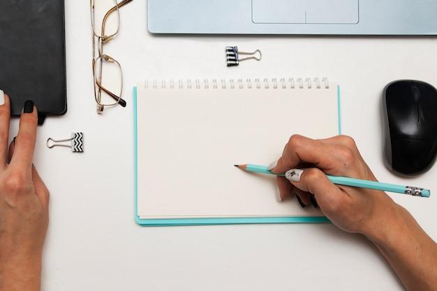 Mulher de negócios faz uma entrada em um caderno em cima da mesa Foto Premium