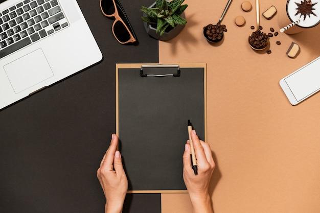 Mulher de negócios fazer papelada, segurar a área de transferência e caneta sobre a vista superior do design de café do espaço de trabalho na moda. layout de papel em branco, laptop, artigos de papelaria na mesa. Foto Premium