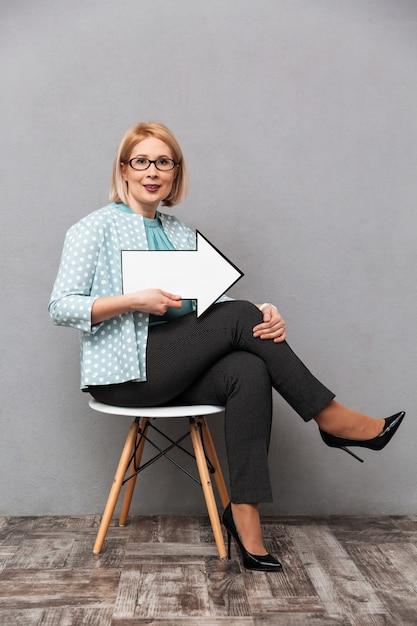 Mulher de negócios feliz apontando com seta. Foto Premium