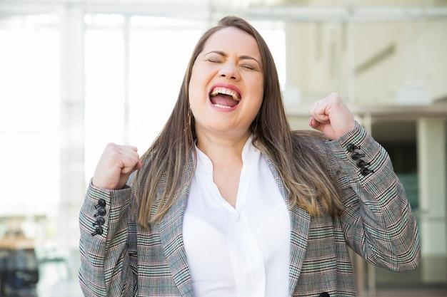 Mulher de negócios feliz bombeamento punhos ao ar livre Foto gratuita
