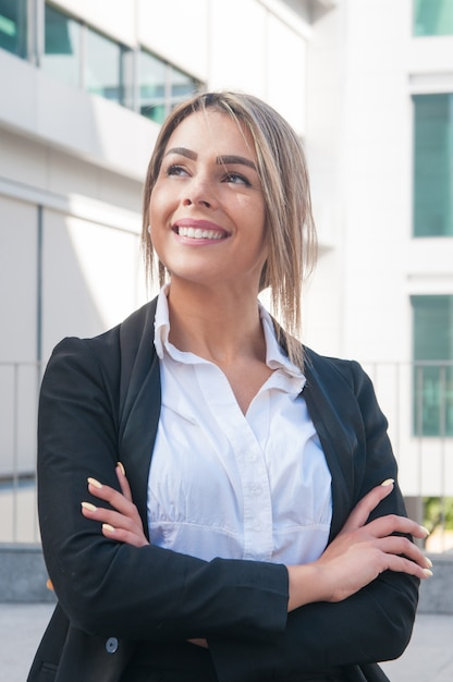 Mulher de negócios feliz em pé ao ar livre Foto gratuita