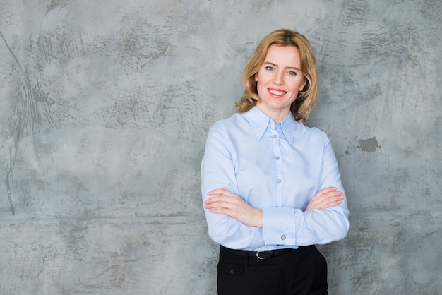Mulher de negócios feliz em pé com os braços cruzados Foto gratuita