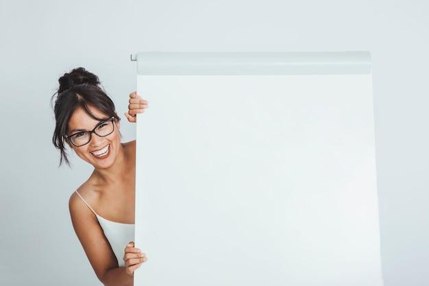 Mulher de negócios feliz escondida atrás do quadro branco Foto gratuita