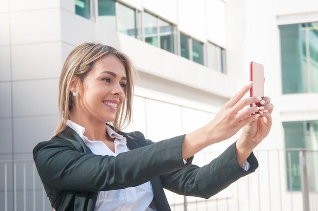 Mulher de negócios feliz falando foto selfie ao ar livre Foto gratuita