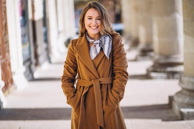 Mulher de negócios feliz no casaco na rua Foto gratuita