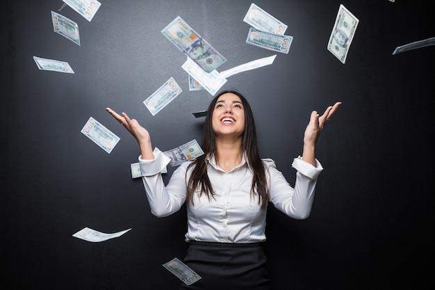 Mulher de negócios feliz sob uma chuva de dinheiro feita de dólares isolados na parede preta Foto gratuita