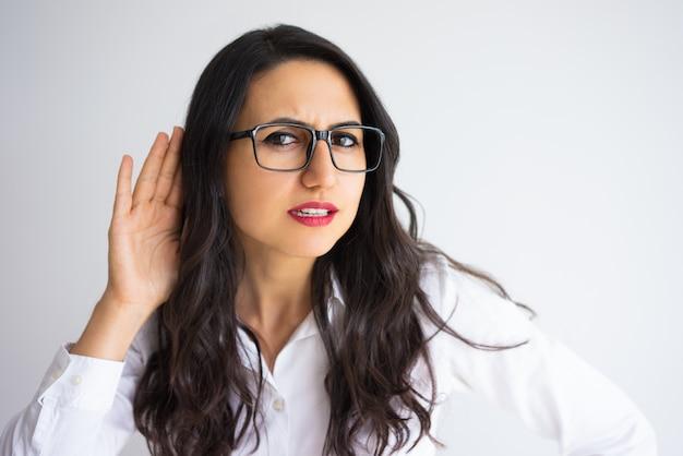Mulher de negócios focada segurando a mão perto da orelha Foto Premium