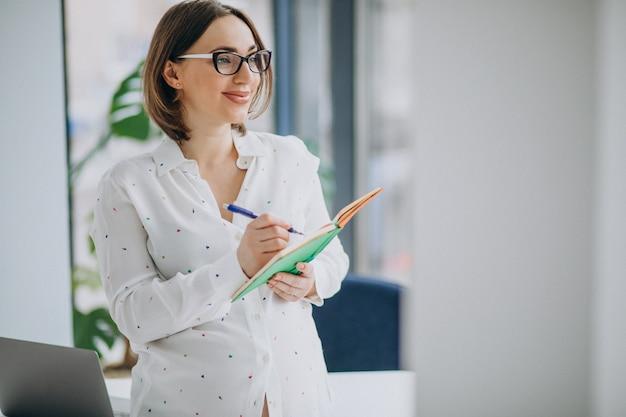 Mulher de negócios grávida jovem em pé no escritório Foto gratuita