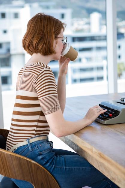 Mulher de negócios hipster sentado aa mesa, bebendo café e digitando Foto Premium