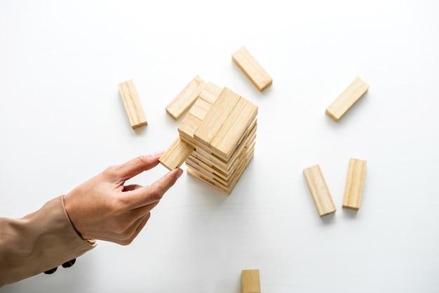 Mulher de negócios inteligente jogar o jogo de madeira, mãos do executivo colocando o bloco de madeira Foto Premium