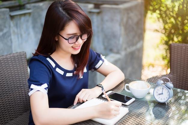 Mulher de negócios jovem asiático escrever uma nota Foto Premium