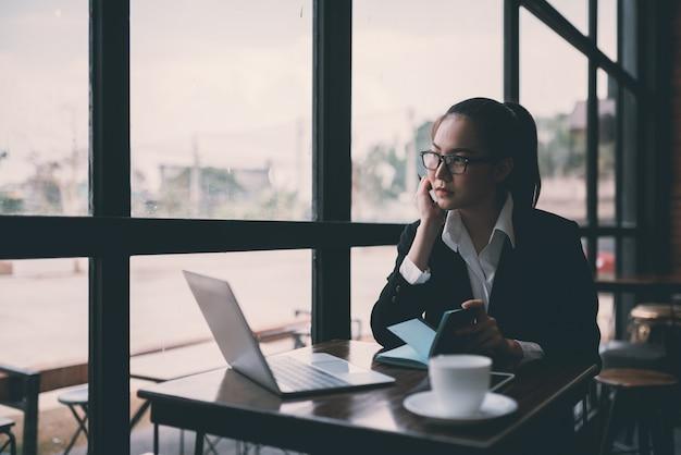 Mulher de negócios jovem bonita sentada na mesa e tomar notas. no café Foto Premium