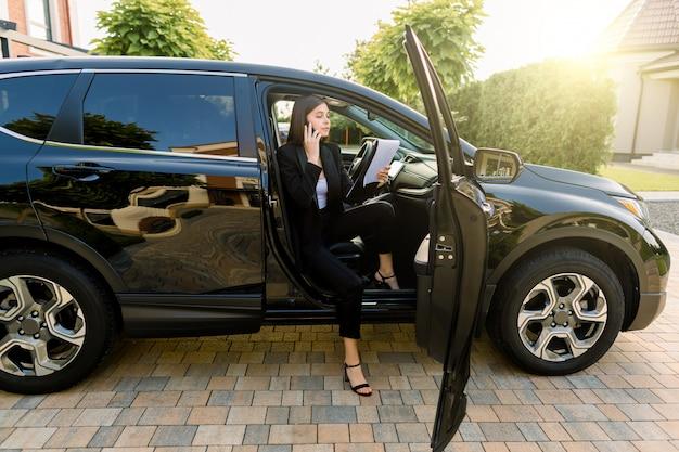 Mulher de negócios jovem bonita terno preto, usando telefone celular e fazendo anotações em papéis, enquanto está sentado no carro com a porta aberta Foto Premium