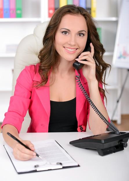 Mulher de negócios jovem confiante falando ao telefone. Foto Premium