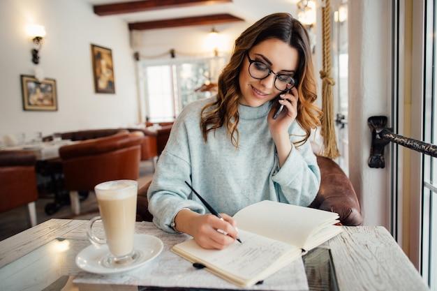 Mulher de negócios jovem em copos levando conversa de negócios no telefone Foto gratuita