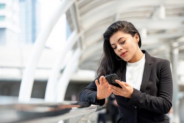Mulher de negócios jovem latina usando smartphone ao ar livre Foto Premium