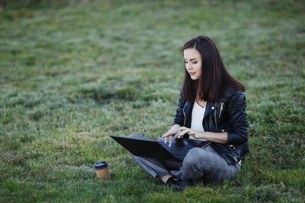 Mulher de negócios jovem sentado e trabalhando no parque com o laptop Foto Premium