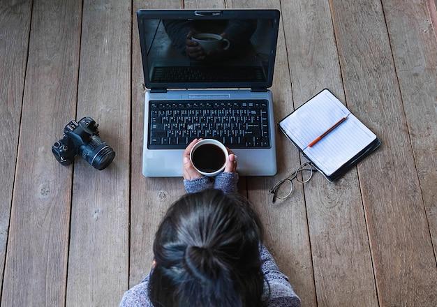 Mulher de negócios jovem sentado no trabalho on-line e café Foto Premium