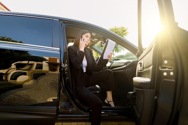 Mulher de negócios jovem sério vestida com roupa formal, conversando com o parceiro via telefone celular e usando a área de transferência enquanto está sentado no automóvel de luxo preto Foto Premium