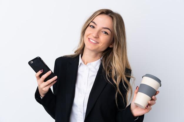 Mulher de negócios jovem sobre parede branca isolada, segurando uma xícara de café e um telefone Foto Premium