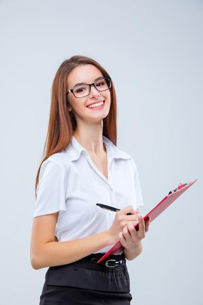 Mulher de negócios jovem sorridente de óculos com caneta e tablet para anotações em um cinza Foto gratuita