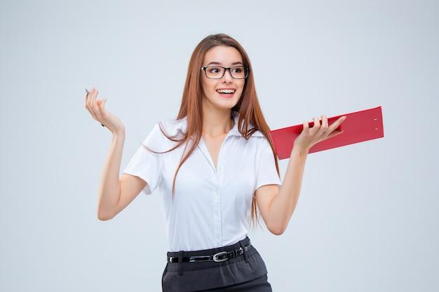 Mulher de negócios jovem sorridente de óculos com caneta e tablet para anotações em um fundo cinza Foto gratuita