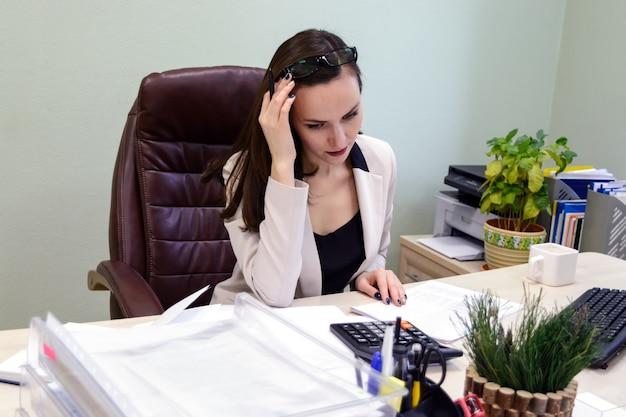 Mulher de negócios jovem trabalhando duro sobre a mesa no estudo, relatório financeiro do economista contabilista Foto Premium