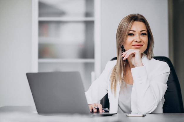 Mulher de negócios jovem trabalhando no laptop em um escritório Foto gratuita