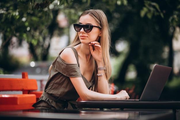Mulher de negócios jovem trabalhando no laptop fora em um café Foto gratuita