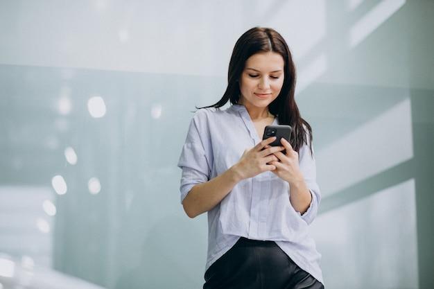 Mulher de negócios jovem usando o telefone no escritório Foto gratuita