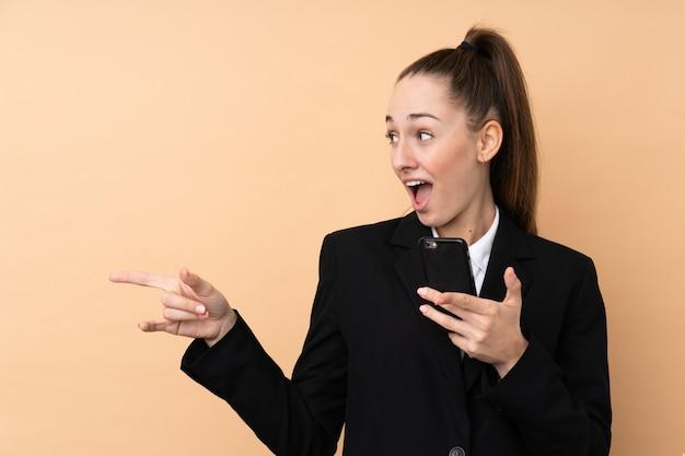 Mulher de negócios jovem usando telefone celular sobre parede isolada surpreendeu e apontando o lado Foto Premium
