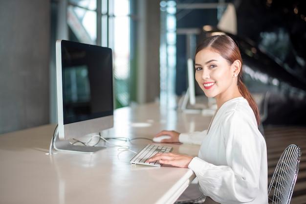 Mulher de negócios linda está trabalhando com seu computador Foto Premium