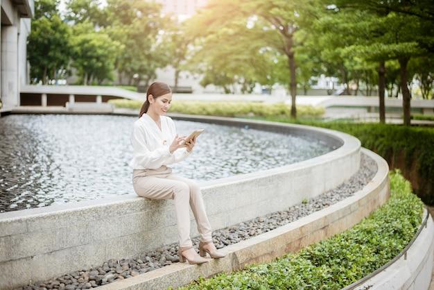 Mulher de negócios linda está trabalhando fora do escritório Foto Premium