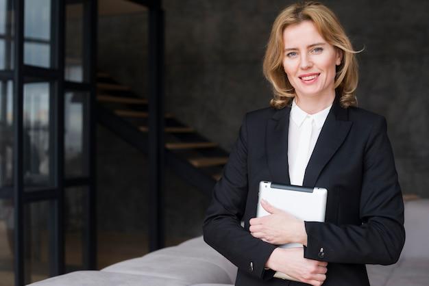Mulher de negócios loiro de terno com tablet Foto gratuita